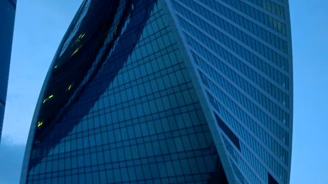 Light in office windows in modern skyscraper. Zoom in FullHD establishing shot video