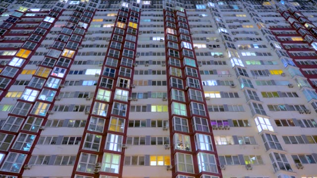 Light in the windows of housings. Turns on and off the light in the windows of houses. Lights of the night city. Time lapse. Business center outdoor.