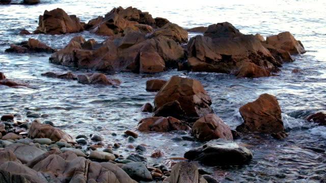 vídeos y material grabado en eventos de stock de luz mar surf en una playa pedregosa y rocas en el agua. - basalto