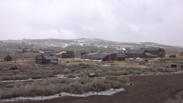 Light snowstorm starts to cover the idyllic ghost town in the rugged landscape.