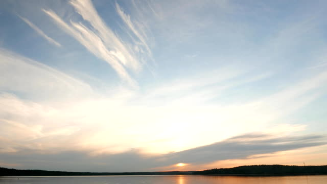 Light stretched clouds over evening sky, lake sunset skies time lapse shot video