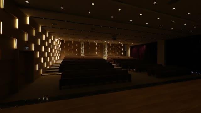 luce accesa/spenta, in sala conferenze vuota con file di posti per spettatori e pubblico. - studio camera video stock e b–roll