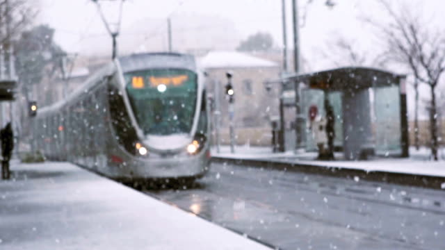 light train coming in slow motion during rare snow in jerusalem - tranvia video stock e b–roll
