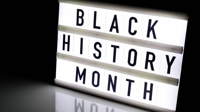 лайтбокс с текстом black history month на темно-черном фоне с зеркальным отражением. сообщение историческое событие. 4k видео. увеличить - black history month стоковые видео и кадры b-roll