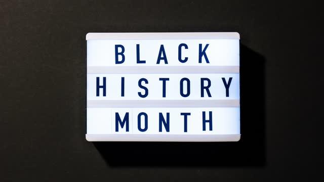 ayna yansıması ile koyu siyah arka plan üzerinde metin si̇yah tari̇h ay ile lightbox. i̇leti geçmiş olay. 4k video. yakınlaştırma - black history month stok videoları ve detay görüntü çekimi
