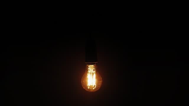 Lightbulb. Black background. A single retro styled modern low energy lightbulb gently moving from side to side against a black background. low lighting stock videos & royalty-free footage