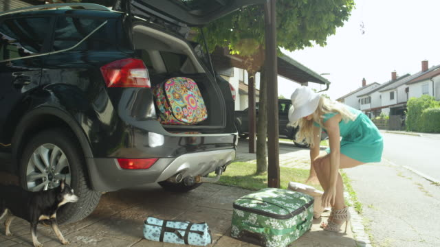LENS FLARE: Lighthearted young woman fails to close the trunk of her black car. LENS FLARE: Lighthearted young woman fails to close the trunk of her black car and her suitcases fall all over the driveway. Female tourist fails to catch travel bags falling from the back of SUV. stuffed stock videos & royalty-free footage