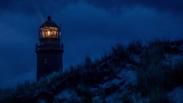 leuchtturm in der dämmerung in der nähe des strandes beleuchtet - leuchtturm stock-videos und b-roll-filmmaterial