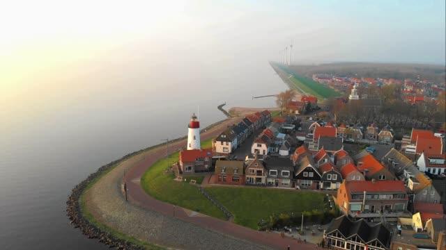 vídeos de stock, filmes e b-roll de farol de urk na praia rochosa no lago ijsselmeer pela antiga ilha urk flevoland holanda, vista de olho de pássaro da antiga vila holandesa urk - sol nascente horizonte drone cidade