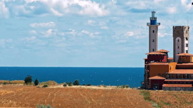 Lighthouse on sand dune against blue sky