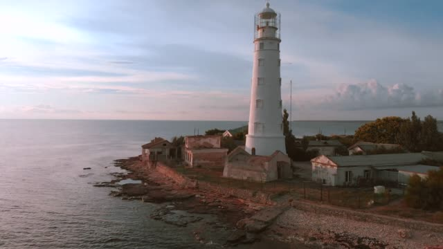 Lighthouse on the cape. beautiful shot from the air, flying over the lighthouse during sunset, beautiful light, scenic landscape sky and sea, Suristic colors. Flying around the lighthouse