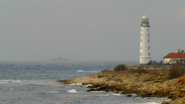 Bидео lighthouse on the coast and warship at sea