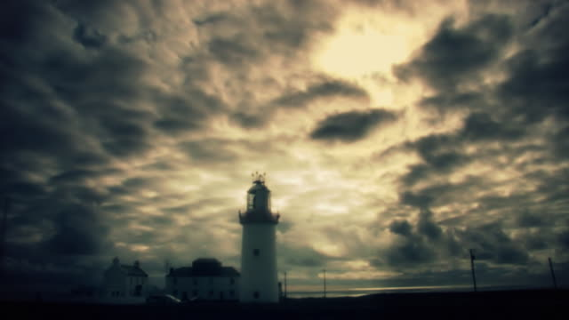 Lighthouse set against moody time lapse sky video