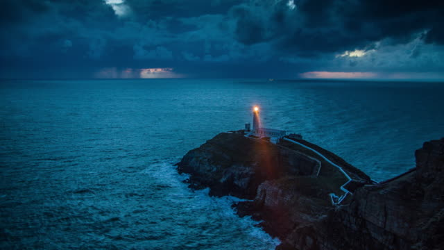 Lighthouse with light beam at stormy coastline