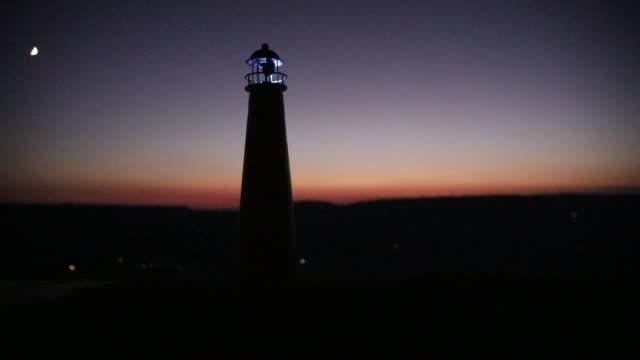 leuchtturm mit lichtstrahl bei sonnenuntergang. alter leuchtturm auf dem berg. tischdekoration. selektiver fokus - leuchtturm stock-videos und b-roll-filmmaterial