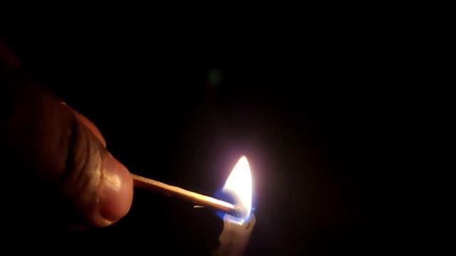 karanlıkta bir mum yakmak. yavaş çekim - mum aydınlatma ürünleri stok videoları ve detay görüntü çekimi