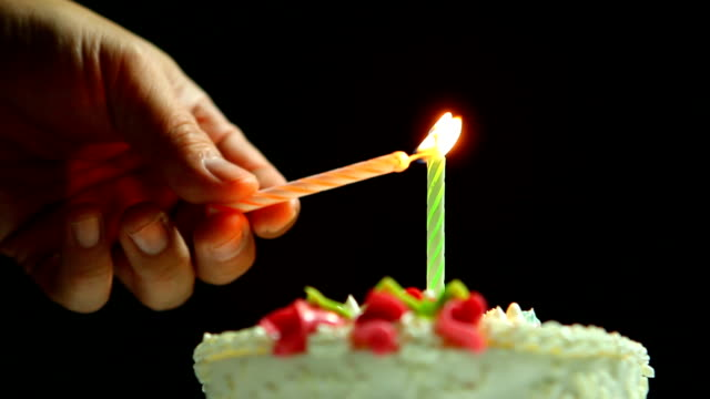 Lighting candle on happy birth day cake