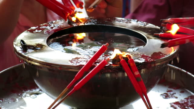 Lighting candles and bundles of incense video