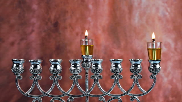 Lighting the first candle on a hanukkah of a burning Chanukah candlestick with candles Menorah a traditional Jewish holiday
