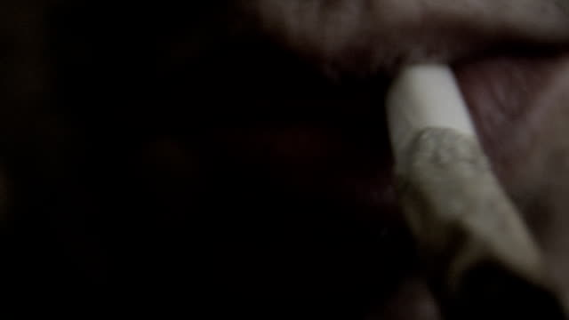 """lighting up a """"roach"""" Extreme close up shot (detail from 4K resolution) of man lighting up the remaining of a marijuana joint and blows smoke until it fills the frame. amazing skin detail, nice puffy smoke. marijuana and hashish, drug smoking addictions. shot on RED camera hashish stock videos & royalty-free footage"""