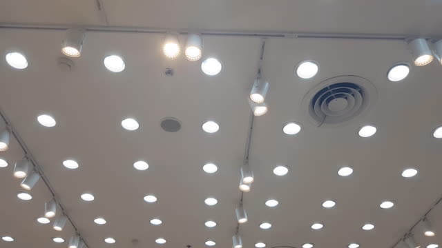lights and ventilation system in long line on ceiling of the dark office industrial building, exhibition hall ceiling - soffitto video stock e b–roll