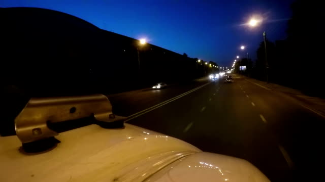 Lights of moving ambulance car flashing in twilight town, high speed necessity video