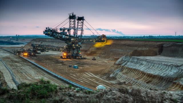 brunkol gruvan med ösregna rullar grävskopan - time lapse tracking shot - excavator bildbanksvideor och videomaterial från bakom kulisserna