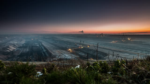 Lignite Surface Mine - Timelapse tracking shot Time lapse tracking shot of a giant lignite open pit mine at dusk. Bucket Wheel Excavators inside the mine are digging coal and sediment. Camera pan over the large surface mine. open cast mine Garzweiler in Germany coal stock videos & royalty-free footage
