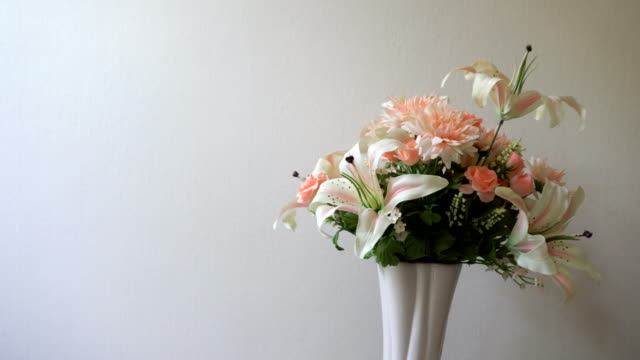 Lilies, roses, carnations flowers in pink vase on white background is rotating. Pastel flower collection presentation