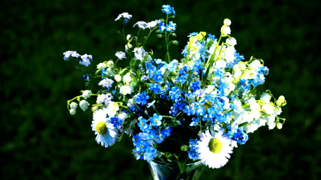 lily of the valleys, forget me nots and daisies wildflowers bouquet loop turning close up video