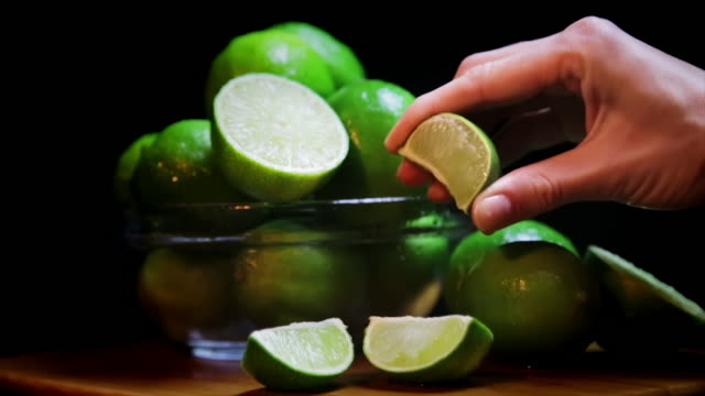 Lime Being Squeezed by Hand Here you have a lime wedge being squeezed by a beautiful hand, juice squirting out among other limes in the background. margarita stock videos & royalty-free footage