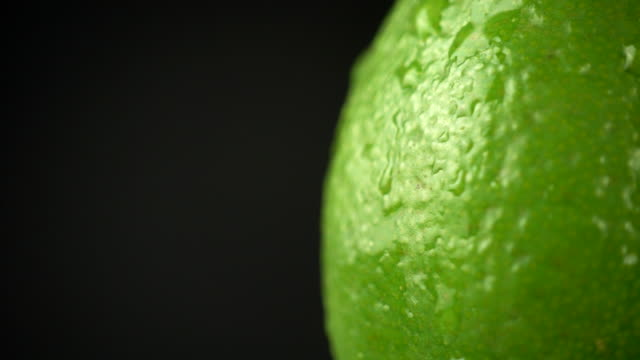 vídeos de stock e filmes b-roll de lime crust with water drops on a black background. water drops on a citrus close up. macro shooting of a citrus. green juicy lime, rotation 4k - lima
