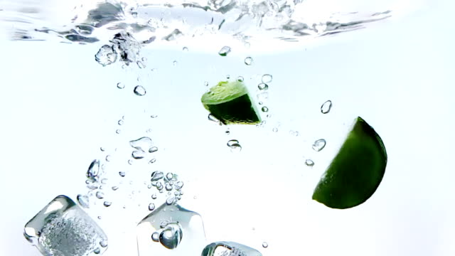 vídeos de stock e filmes b-roll de lime fruit and ice cubes splash falling down into white cocktail and water drinking glass, shot in slow motion on white background, fun, nutrition and drink - bebida fresca