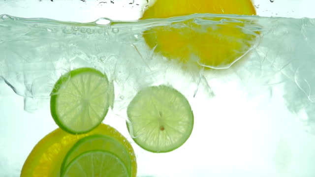 Lime, Lemon and orange slices drop in the ice water. Close up. Slow motion. Lime, Lemon and orange slices drop in the ice water. Front view. Close up. Slow motion. citrus fruit videos stock videos & royalty-free footage