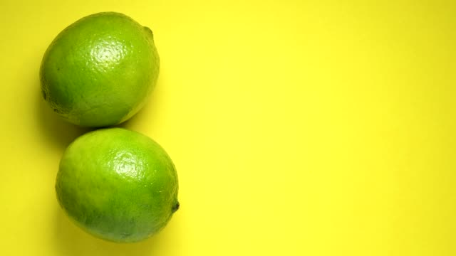 lime rolling on yellow background top view - rotolare video stock e b–roll