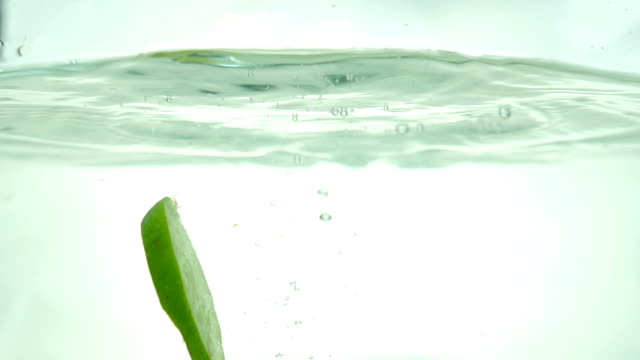 Lime slices drop in the water. Close up. Slow motion. video