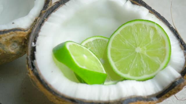 Limettenscheiben fallen in einer Kokosnuss Hälfte in Zeitlupe – Video