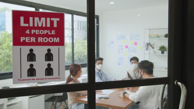 Limit people in meeting room sign over asian business people wear face mask working and meeting in office to protect infection of coronavirus covid-10 after lockdown, reopen new normal office concept