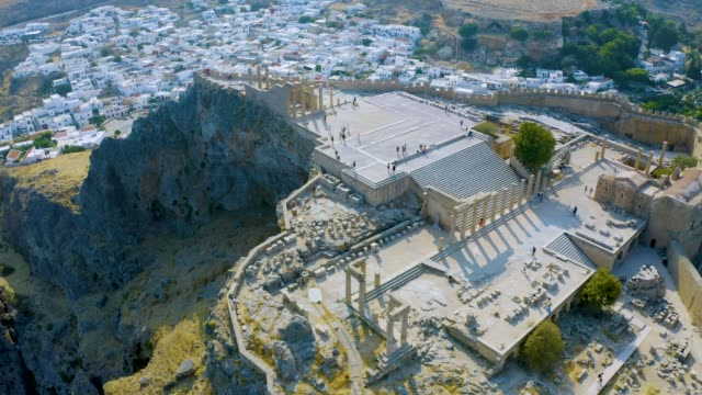 Lindos acropolis. Ancient fortress on top of Lindos village. Rhodes island, Dodecanese, Greece. 4K aerial video taken by drone