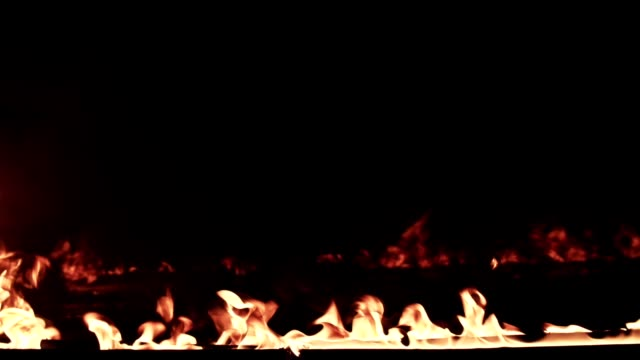 vídeos de stock e filmes b-roll de a line of fire burning in the dark place in slow motion - inflamável