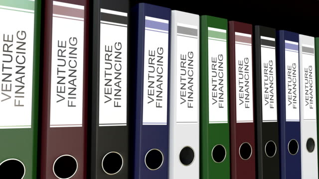 Line of multicolor office binders with Venture financing tags. FullHD seamless loop clip video