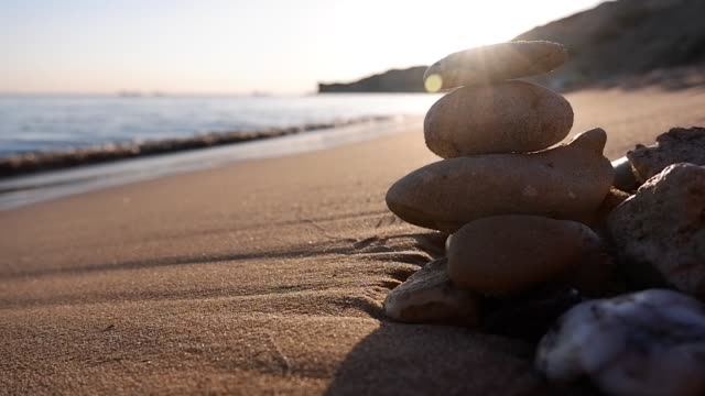 Lined sea stones in a row on the sea shore in front of the setting sun.