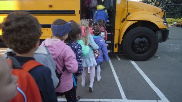 Lined up elementary age kids boarding school bus Back view of diverse little students getting on yellow school bus one after another to go home. Preadolescent schoolchildren patiently waiting in line to enter school bus after studies primary school stock videos & royalty-free footage