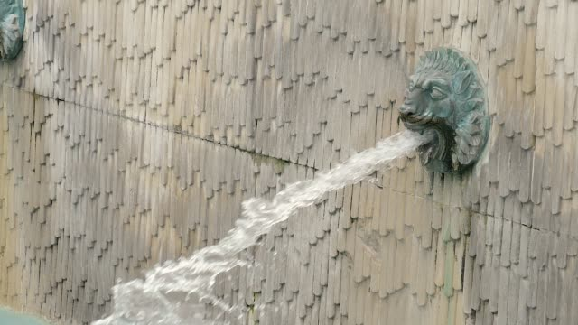 Lion head water fountains spitting water. Slow