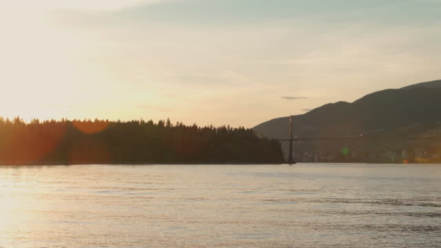 Lions Gate Bridge over Vancouver Harbor at sunset. The remote view from Stanley Park, Vancouver, British Columbia, Canada.