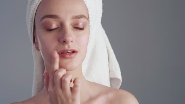 lip moisturizing skincare woman applying balm Lip moisturizing. Skincare cosmetic product. Beauty hygiene. Woman with perfect face skin nude makeup towel on head applying nourishing balm after bath isolated on gray. lip balm stock videos & royalty-free footage