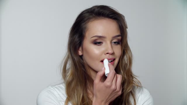 Lip Skin Care. Woman With Beauty Makeup Applying Balsam On Lips