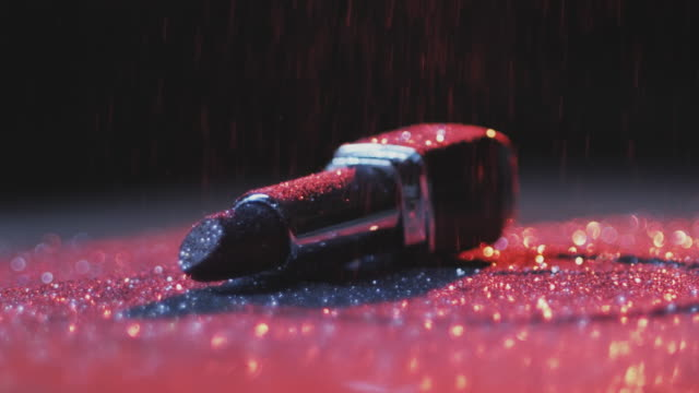 Lipstick and Glitter Illuminated with Neon Lights Close up of lipstick lying on table against black background and glitter pouring on it lipstick stock videos & royalty-free footage