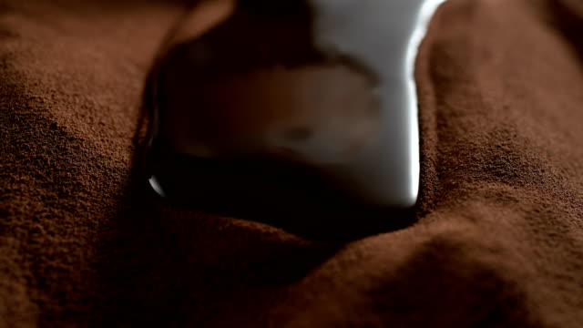 liquid chocolate flowing on cocoa powder. super slow motion - cioccolato video stock e b–roll