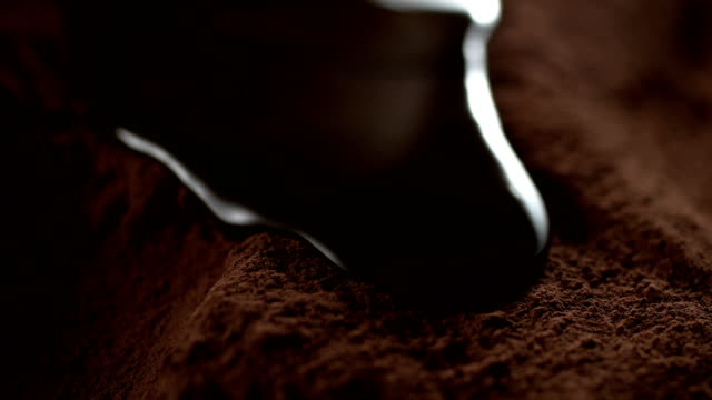 Liquid chocolate flowing on cocoa powder. Super slow motion